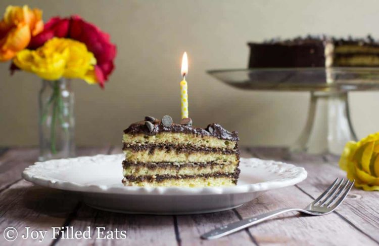 slice of yellow birthday cake with chocolate icing on a white plate with one lit yellow candle sticking in the slice. Plate is set next to a fork and cake platter with remaining cake