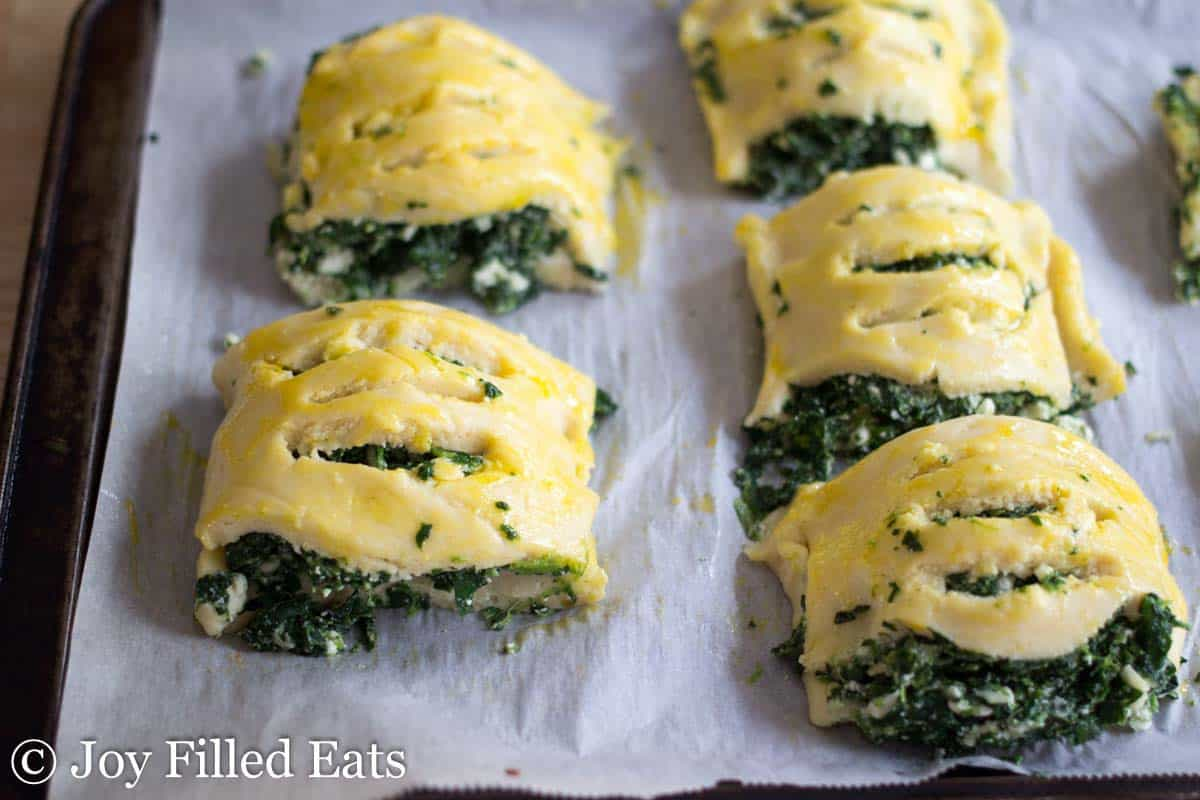 spinach and feta shaped pastries lined on parchment paper before baking