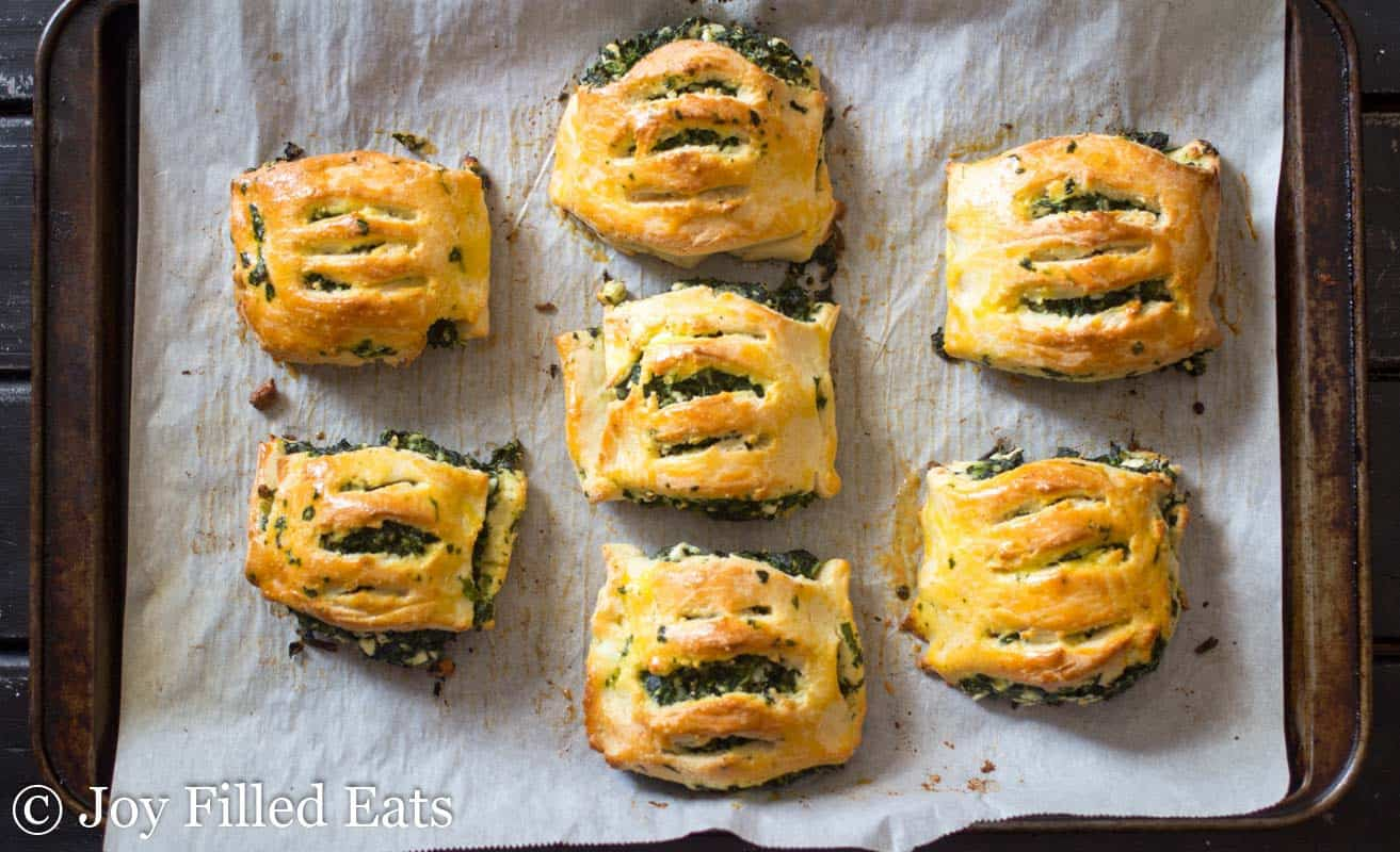 overhead view of spinach and feta pastries arranged on a parchment lined sheet pan