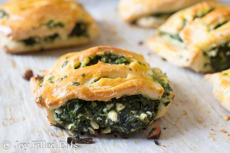 close up on spinach and feta pastries lined on parchment paper