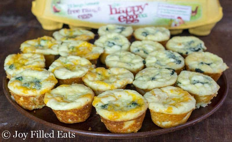 plate filled with mini quiches set next to a yellow egg carton