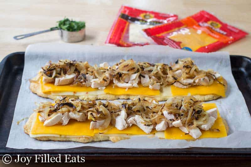 Layers of the toppings on the Zesty Chicken & Onion Low Carb Flatbread waiting to be baked