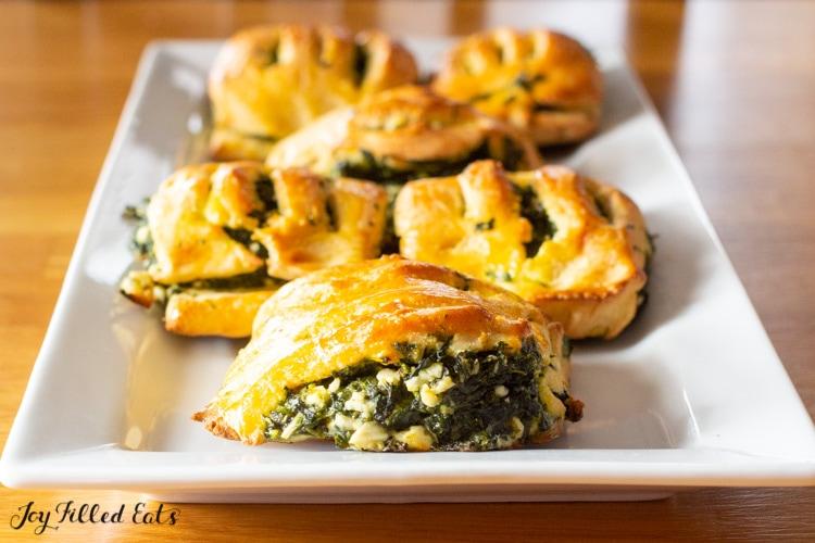spinach & feta pastries on a white rectangular platter