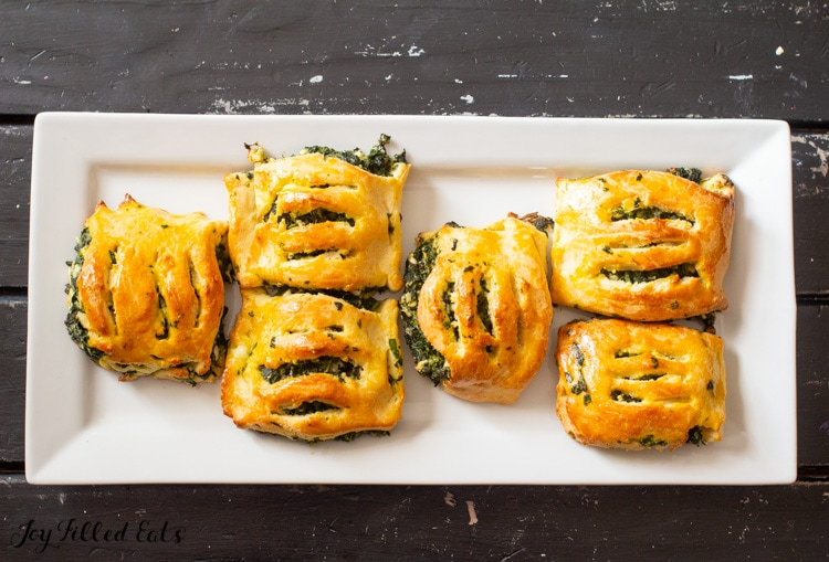 overhead view of spinach & feta pastries arranged on a white platter