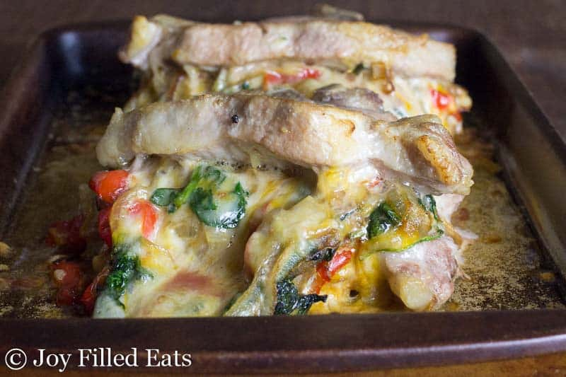 Cheesy Stuffed Pork Chops with Spinach, Peppers, & Onions with gooey cheese coming out