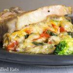 keto stuffed pork chops on a black plate with broccoli