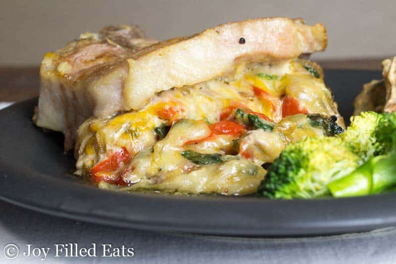 A Cheesy Spinach Stuffed Pork Chops with Peppers & Onions on a black plate