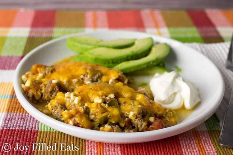 Mexican taco casserole serving on a plate with sour cream and avocado slices