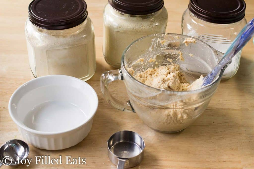 mini snickerdoodle layer cake batter in a mixing bowl next to a small ramekin and surrounded by ingredients