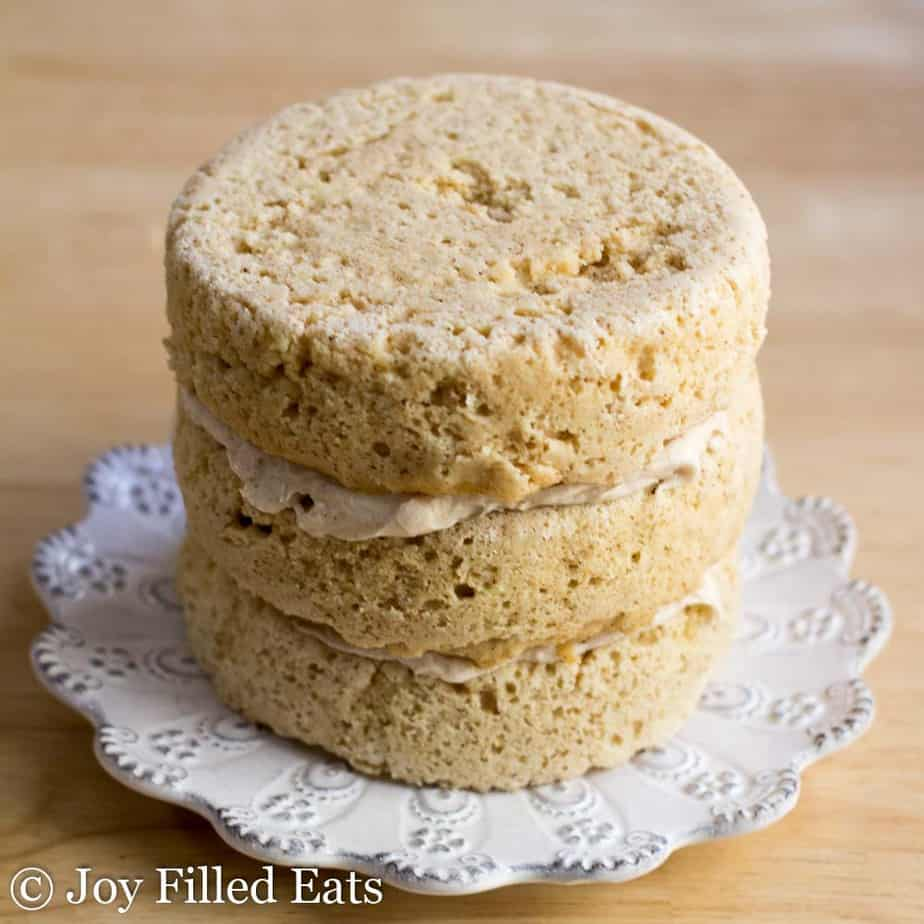 three layers of mini snickerdoodle layer cake held together with frosted filing on a white plate