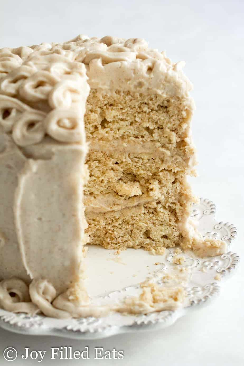 close up on layers of mini snickerdoodle layer cake with slice missing on a white plate