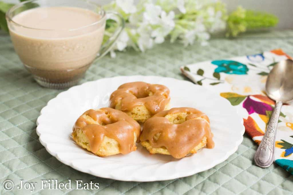 three glazed mini browned butter caramel donuts on a white plate next to a glass mug of coffee
