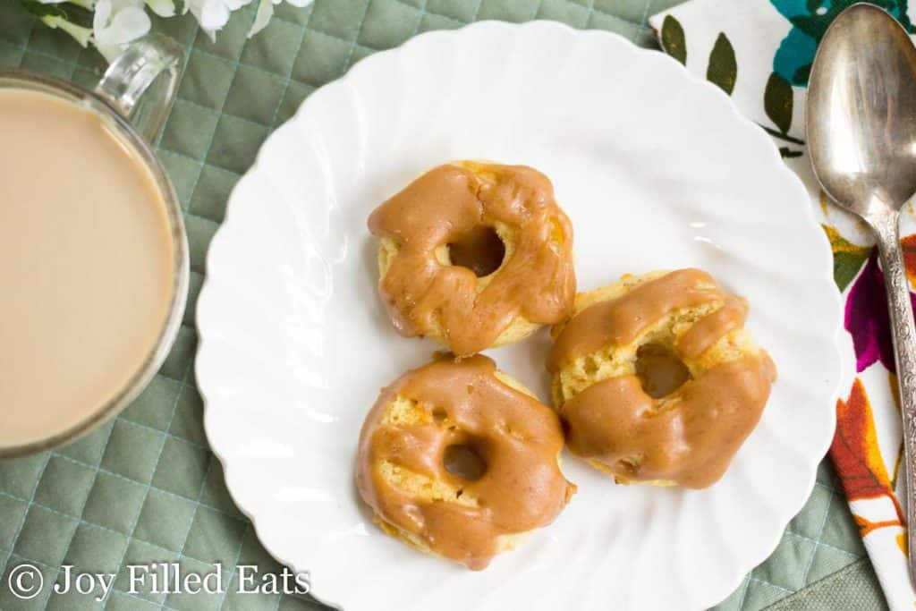 three mini browned butter caramel donuts set on a white plate from above