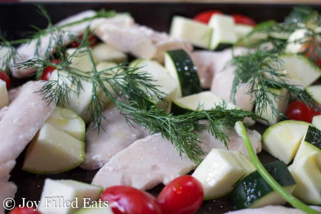 close up on fresh dill, vegetables and chicken on a sheet pan to be roasted