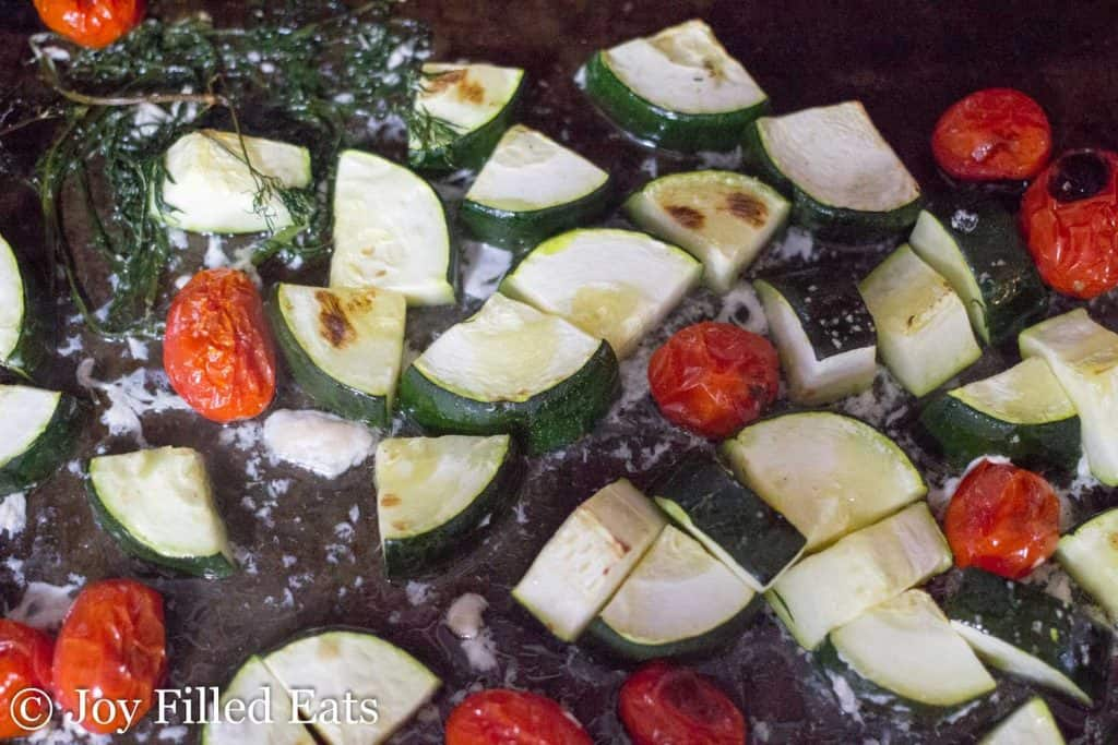 cooked zucchini tomatoes and dill on a sheet pan
