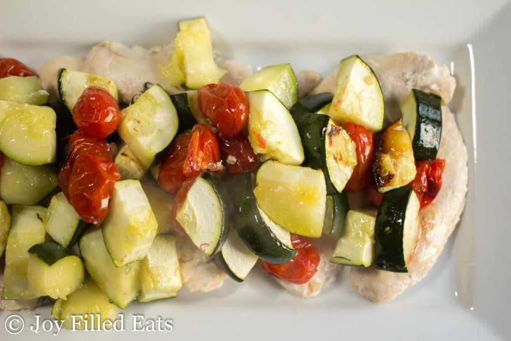 Baked Greek Chicken with veggies on a white plate
