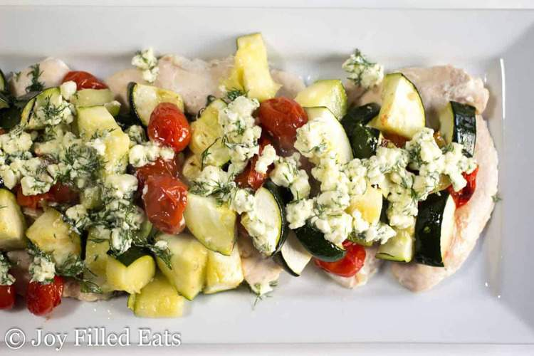overhead view of platter with baked Greek chicken with feta & dill