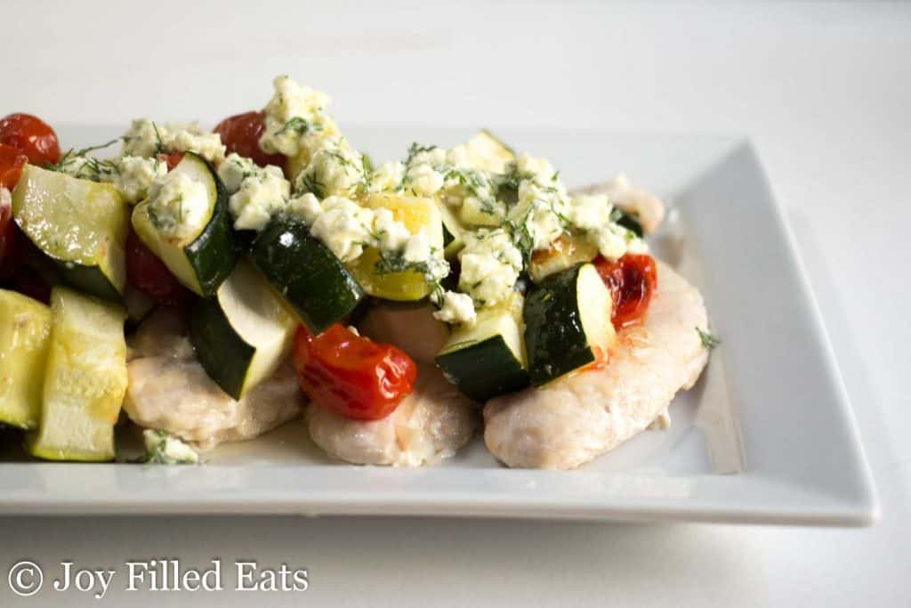 Baked Greek Chicken topped with roast zucchini on a white platter