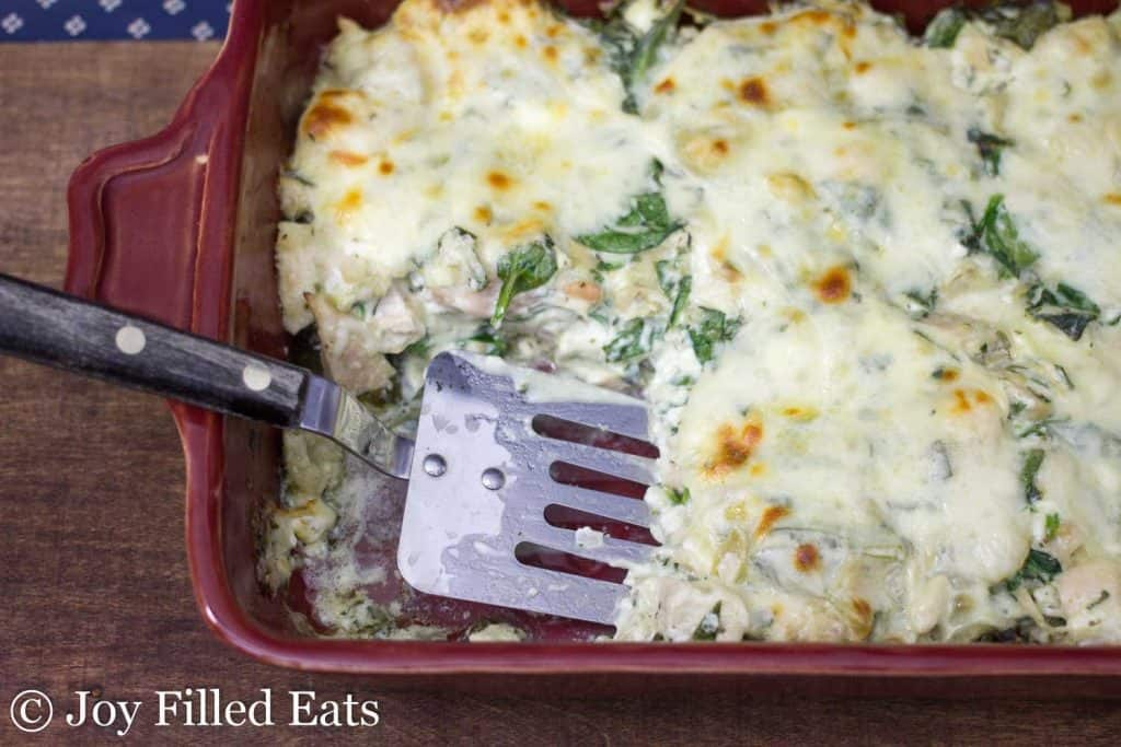 Spinach & Artichoke Chicken Casserole baked in a red casserole dish with a spatula.
