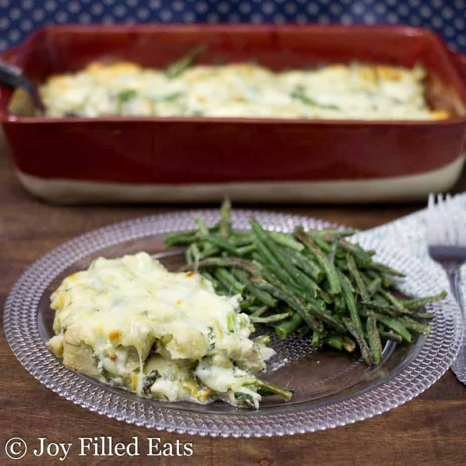 A serving of Spinach & Artichoke Chicken Casserole on a glass plate with green beans. A red casserole dish in the background.