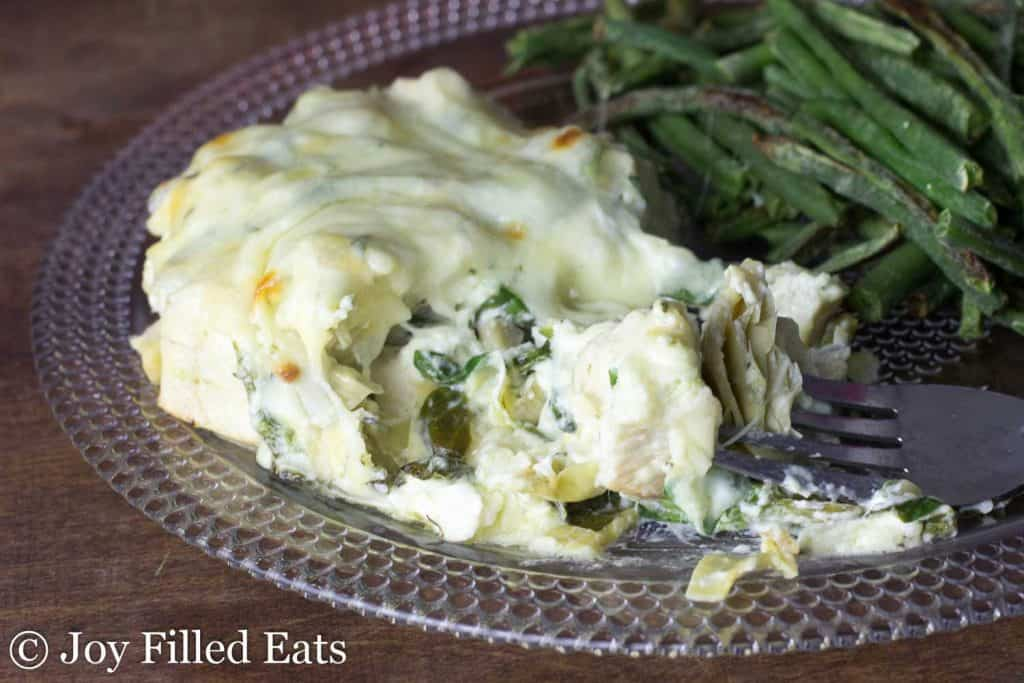 Close up of the Spinach & Artichoke Chicken Casserole on a glass plate with a side of green beans.