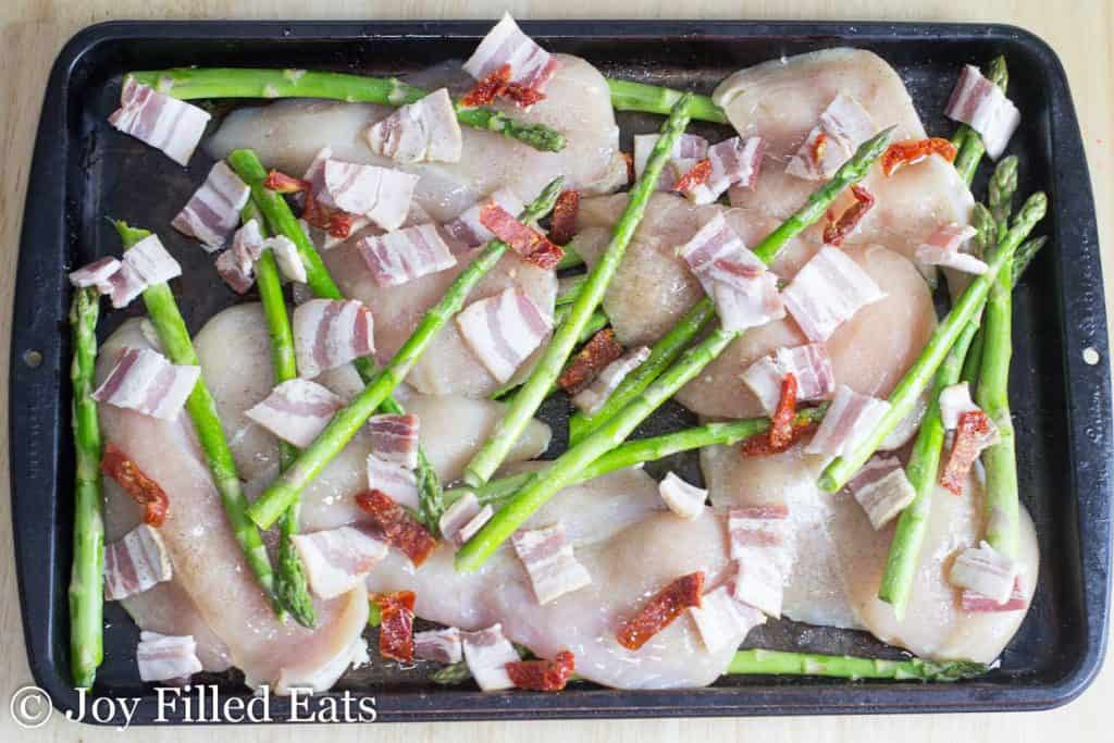 a large rimmed baking sheet with raw chicken asparagus sundried tomatoes and bacon