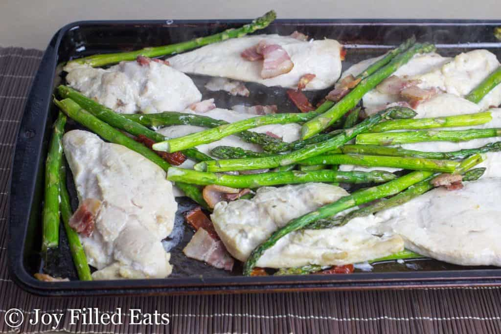 baked chicken asparagus and bacon on a rimmed baking sheet