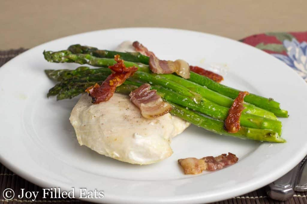 chicken and asparagus sheet pan dinner on a white plate with fork and knife