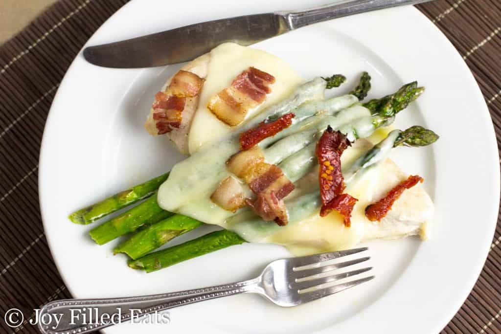 chicken and asparagus sheet pan dinner topped with bacon bits on a plate with fork