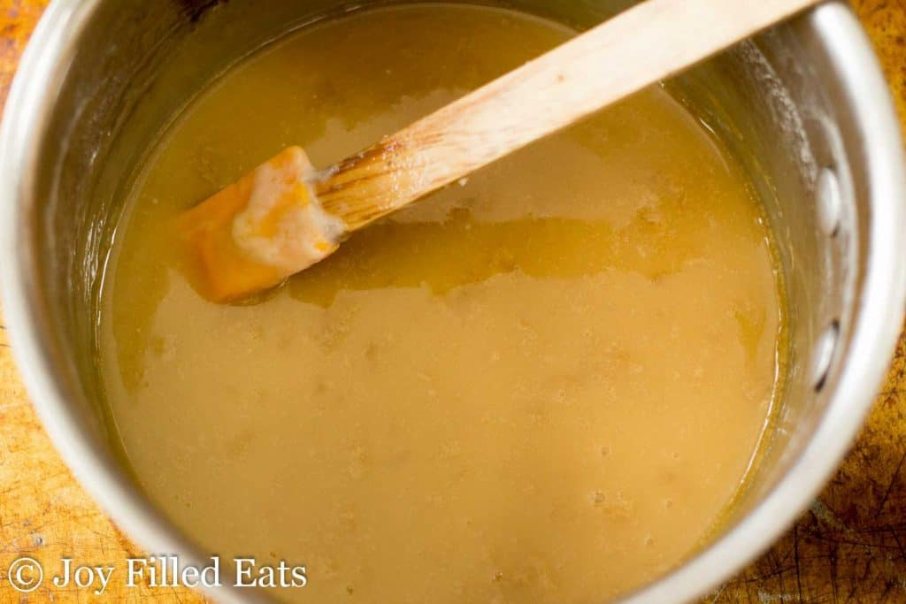 overhead view of saucepan full of caramel sauce with spatula