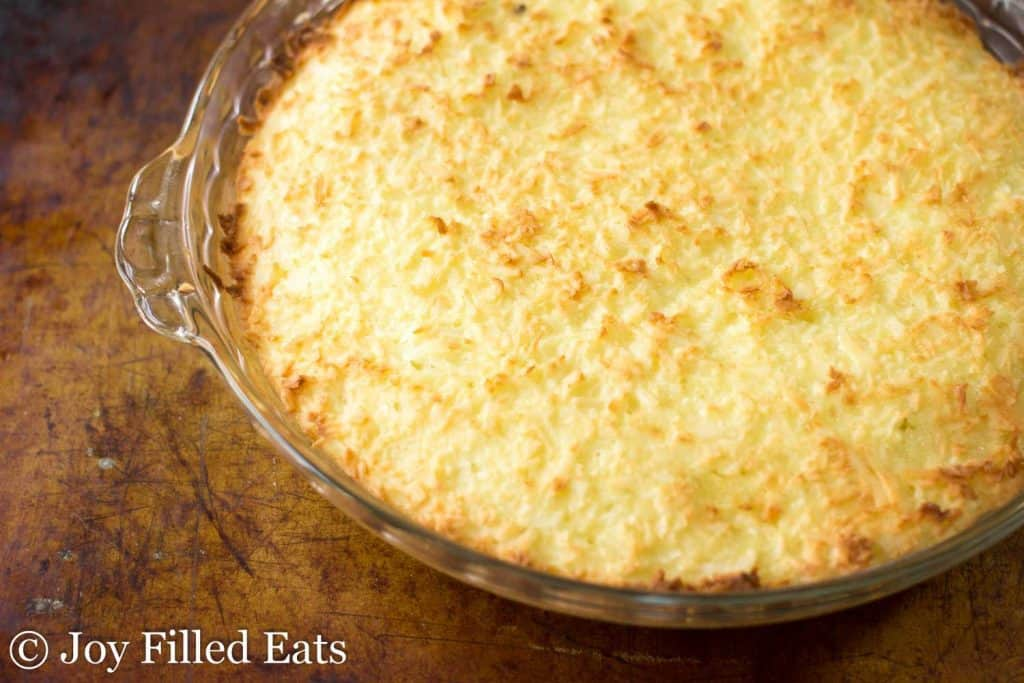 top coconut cake layer in pie dish for chocolate caramel Samoa cookie coconut pie