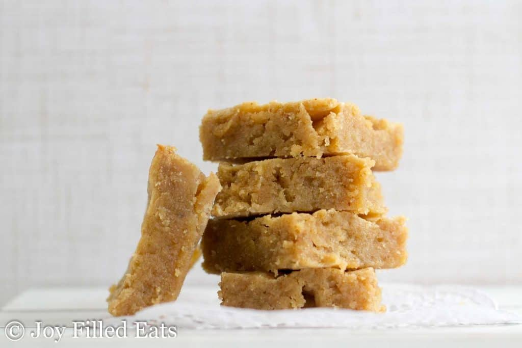 White Chocolate Peanut Butter Keto Blondies in a pile on a white background