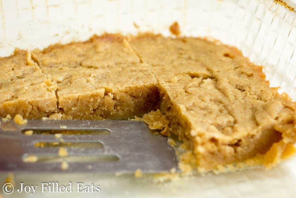 serving spatula in a baking dish lined with pre-cut white chocolate peanut butter blondies