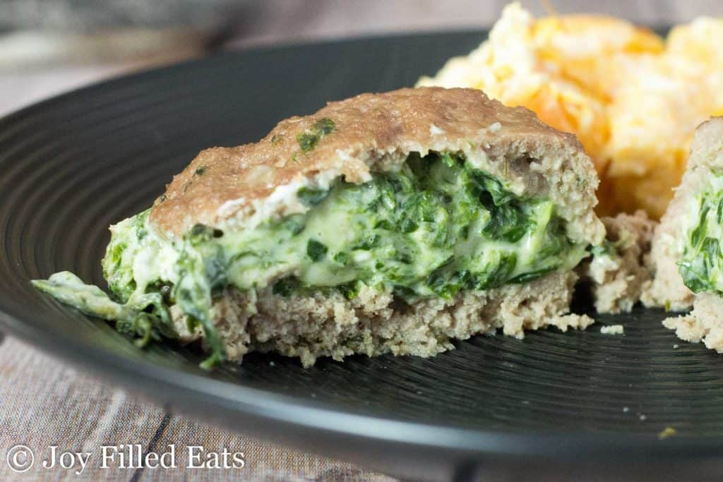 Stuffed Turkey Burgers with Spinach & Three Cheeses on a black plate