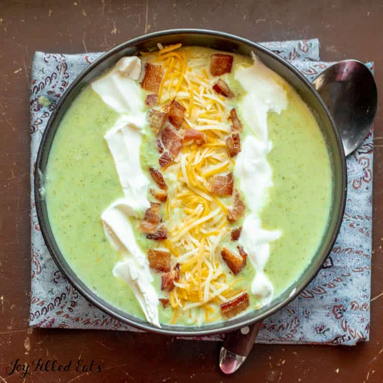 black bowl of Low Carb Broccoli Cheese Soup with Bacon cheddar and sour cream on top