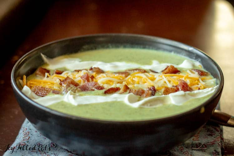 black bowl of keto broccoli cheddar soup with Bacon cheddar and sour cream on top
