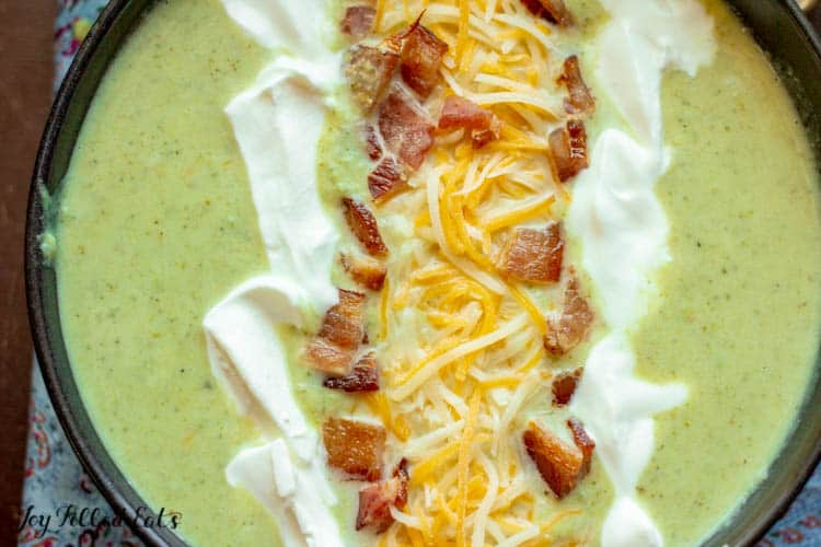 close up of a black bowl of Low Carb Broccoli Cheese Soup with Bacon cheddar and sour cream on top