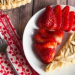 slice of almond tart on a plate with sliced strawberries set next to a fork and napkin