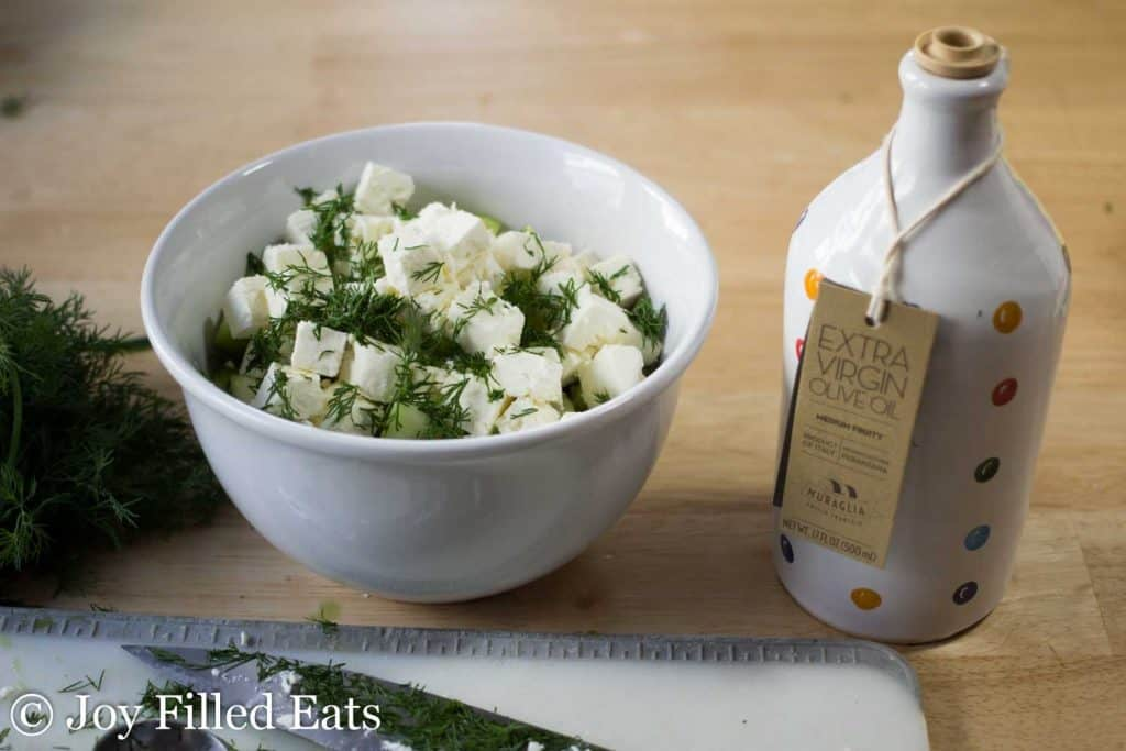 bowl of feta cheese and dill next to a jar of extra virgin olive oil