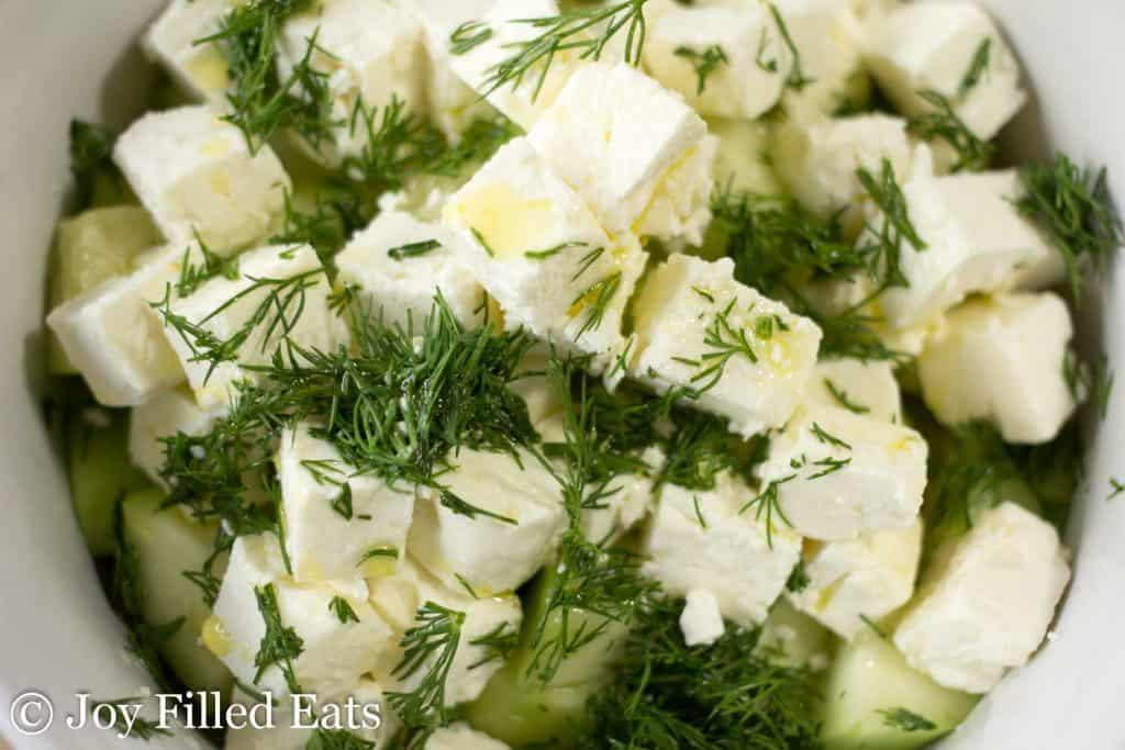 feta cheese and dill in a white bowl close up