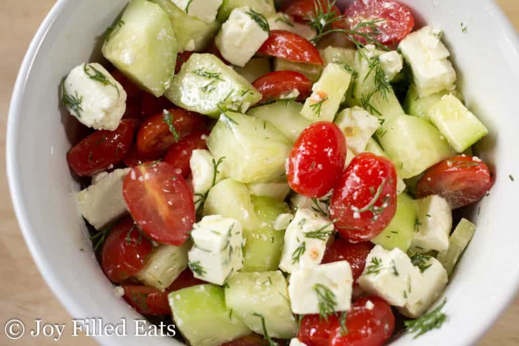 simple Greek tomato & cucumber salad in a white bowl close up