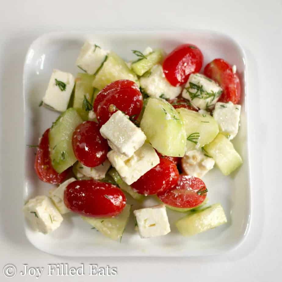 overhead view of simple Greek tomato salad on square white plate