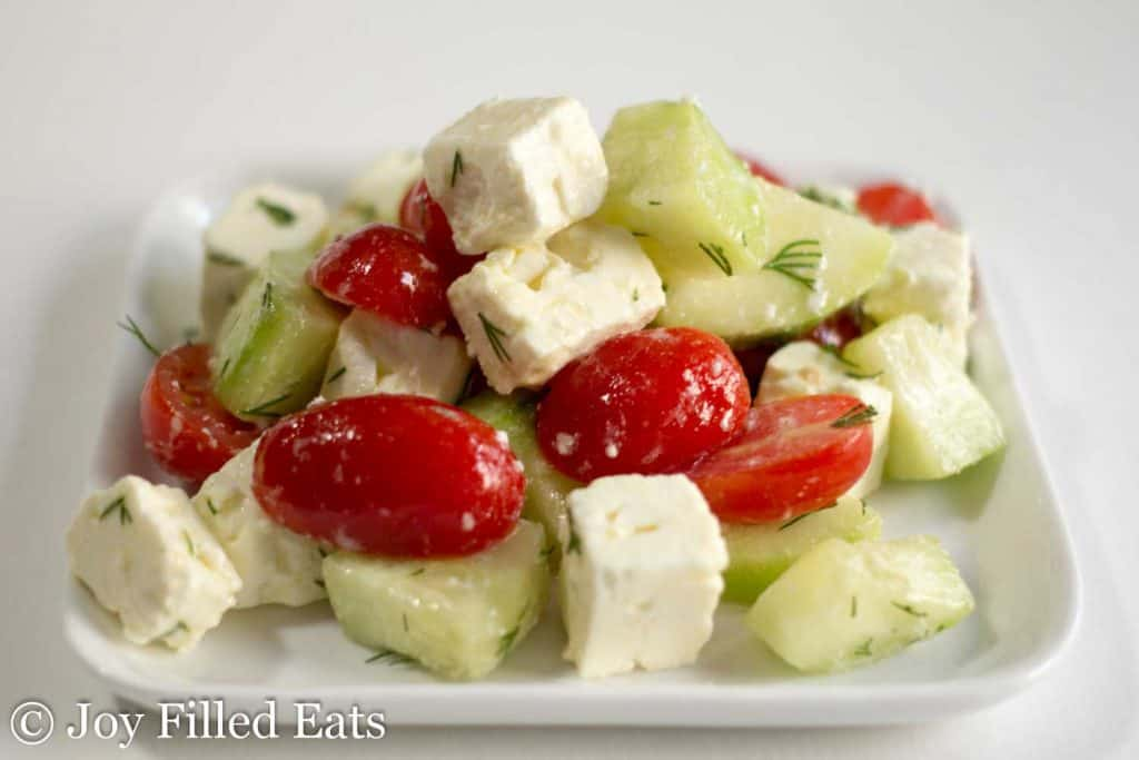 simple greek tomato salad on white square plate