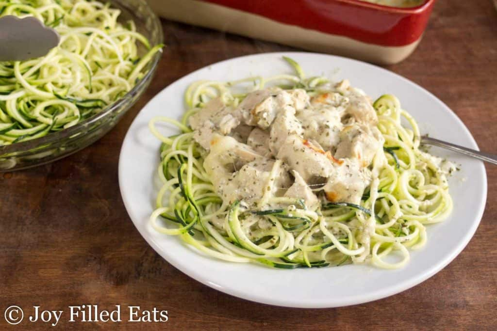 Easy Mozzarella & Pesto Chicken Casserole on a white plate on top of zucchini noodles.