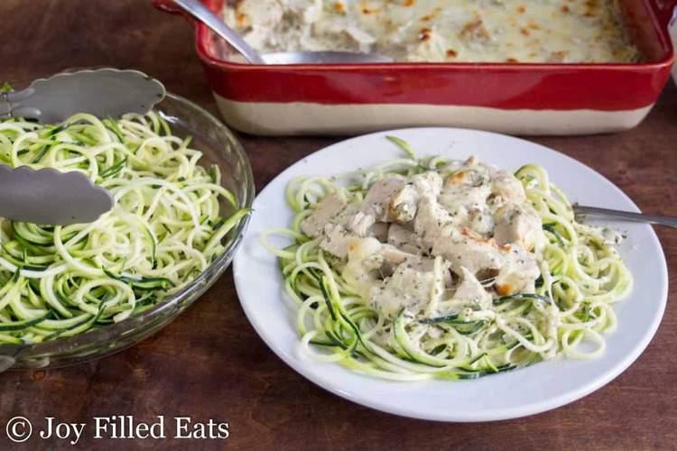 mozzarella & pesto chicken casserole topped on zucchini noodles on a plate set net to a platter of more zucchini noodles and casserole dish
