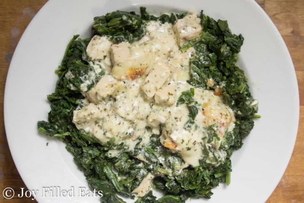 Easy Mozzarella & Pesto Chicken Casserole on top of spinach on a white plate.