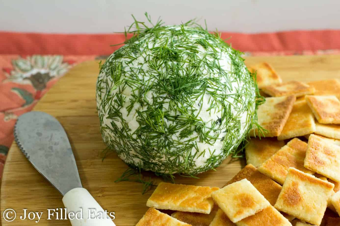 large feta & dill cheese ball set on a cutting board surrounded by crackers and a cheese knife