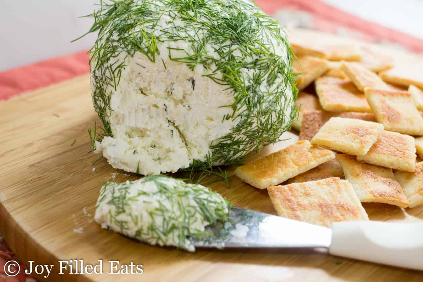 large ball of feta and dill cheese set on a cutting board next to a cheese knife with a slice of cheese ball on it