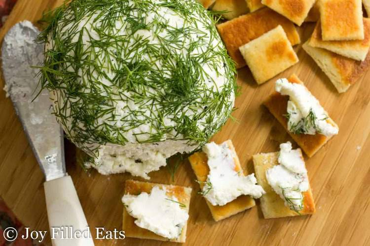 large Feta & dill Cheese ball on a cutting board with crackers and crackers spread with cheese