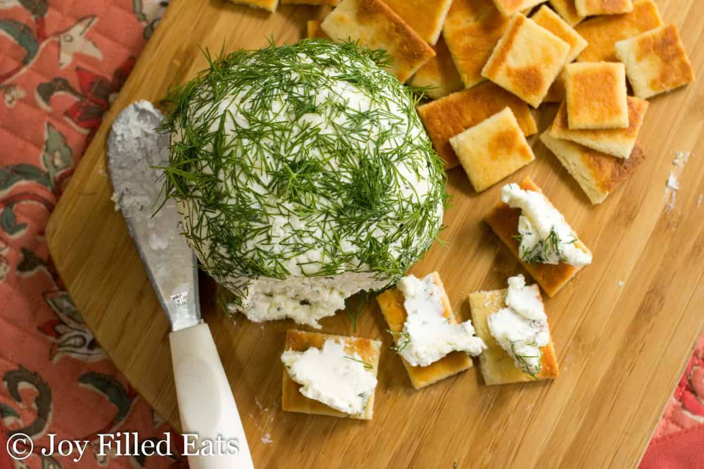 large Feta & dill Cheese ball on a cutting board with crackers and crackers spread with cheese from above